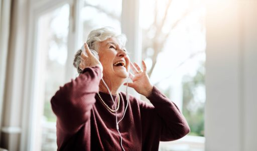 Ederly woman uses digital device at health care_headphones_Hublet